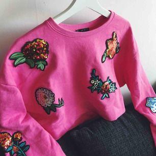 Oversized starkt rosa sweater med paljettblommor utspridda i härliga färger. Använd en gång. Kortare passform alltså cropped.