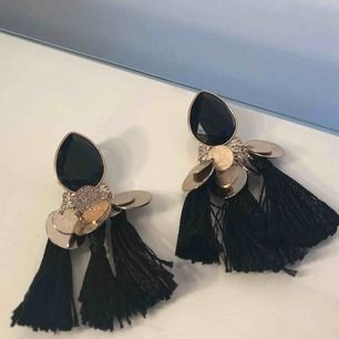 Svarta örhängen med tofsar nertill, guld detaljer.