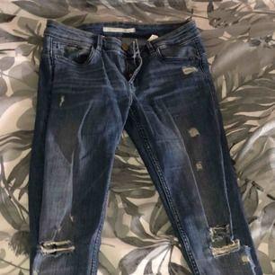 ett par trasiga jeans från zara med slitningar lite överallt. Det är någon push up modell och normal midja. Sitter snyggt på och är väldigt sköna! snyggt, Det har en början till hål där bak på byxan men går att laga.