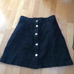 Superfin jeanskjol från monki. knappar och två fickor på framsidan.