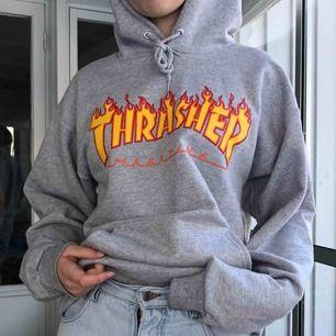 En grå fläckfri thrasher hoodie, med röd orangeast/gult tryck. Knappt använd, köpare står för frakt