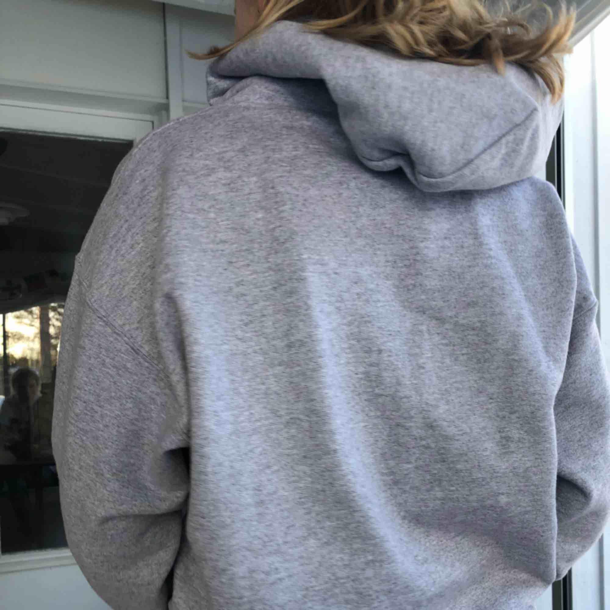 En grå fläckfri thrasher hoodie, med röd orangeast/gult tryck. Knappt använd, köpare står för frakt. Huvtröjor & Träningströjor.