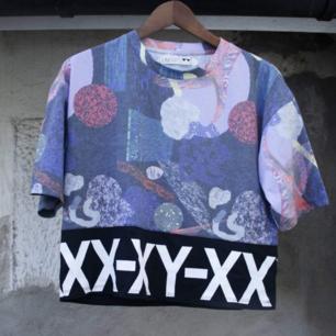 Oversize t-shirt från Junkyard XX-XY. Lite kortare och större modell för att vara en S. (Jag är stl M) Snygg till hög kjol eller höga byxor. Snyggt mönstrat typ upptill och svart tyg runt hela. Bra begagnat skick. Frakt 36kr