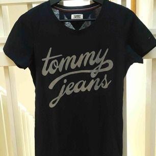 Tommy Hilfiger t-shirt. Marinblå med vitt tryck. Använd en gång. Ganska liten i storlek och passar därför även Medium. Längre i modellen.