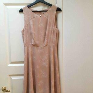 Beige/sandrosa klänning från MQ i storlek 40. Använd sparsamt. Slutar vid knäna med en knapp vid bröstet. Dragkedja på ryggen. Blommigt mönster.