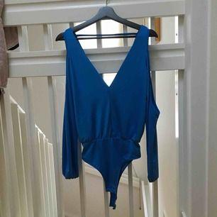 En havsblå body från Gina. Använd en gång. Mycket sexig och frän topp som går att matcha till exakt vad som helst. Öppen rygg, vid v-ringning och öppna överarmar. Den perfekta sommartoppen!