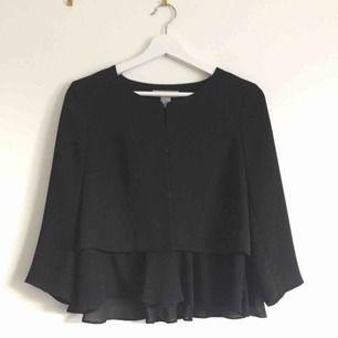 Klassisk svart blus från H&M som går att knäppa eller ha öppen, med volang nedtill. Köparen står för frakt!
