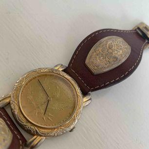 Vintage-klocka i brunt läder och guld Behöver nytt batteri Skickas mot fraktkostnad
