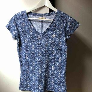Blå mönstrad t-shirt med v-formad hals från Hollister. Köpt i London 2013, använd ca 5 ggr, i bra skick! Köparen står för frakten, swish🌷