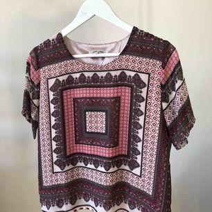 Gwen print top. Rosa/lila-mönstrad med längre t-shirt ärm. Tunt material, silkig innertopp. Rak, kort och rymlig modell. Normal i storlek, stum i materialet. Fint skick men används inte - därav sälj. Material: 100% polyester