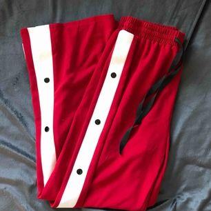 Röda trackpants / popper pants från Missguided. Passar en XS-M tack vare resår och knytmidja. Högmidjade och hellånga.