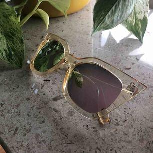 Stentuffa solbrillor. Inköpta i USA. Ljusgula plastbågar med rosaskimrande spegelglas. Kan mötas upp i Stockholms innerstad, annars står köparen för fraktkostnaden.