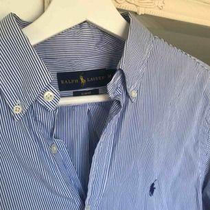 Herr skjorta från Ralph Lauren i slimfit. Storlek medium, fint skick! Inga skavanker🤩 blå och vit randig! Tar swish och kan fraktas🥰