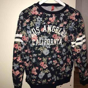 """En blommig """"hoodie"""" där det står """"Los Angeles California"""" på. Bra skick"""