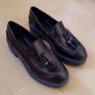 Rödsvarta loafers i skinn från Zara. Det är lite platå på dem och detaljer med nitar. Använda 1 gång men säljer dom nu för att jag känner att de är förstora.