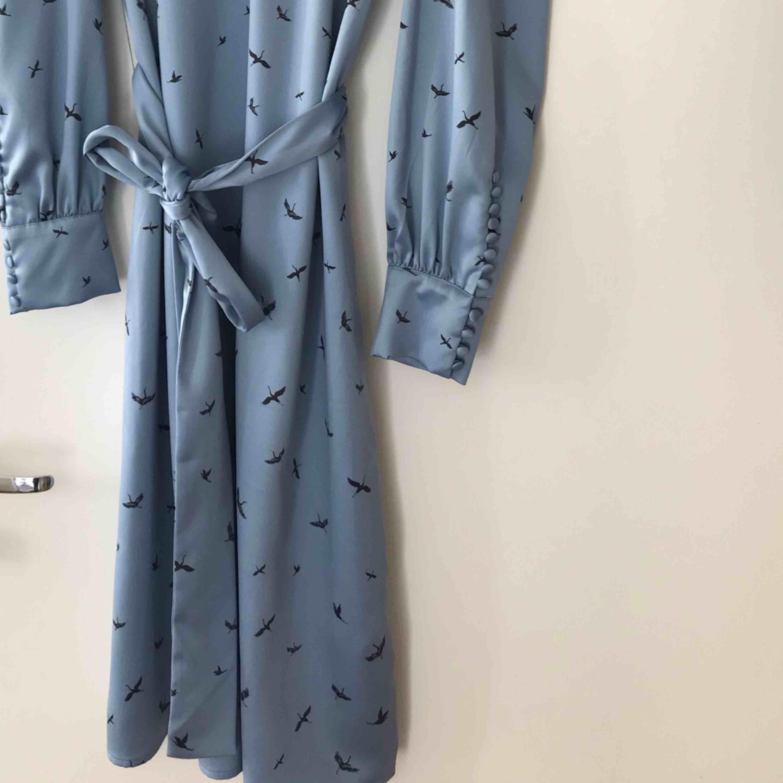Satin klänning med fina detaljer vid ärmarna samt tillhörande bälte. Är mitt i en garderobsrensning annars hade jag aldrig sålt denna pärla. Aldrig använd. . Klänningar.