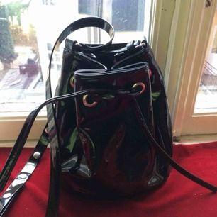 Criss-body väska i lack från Monki. Oanvänd