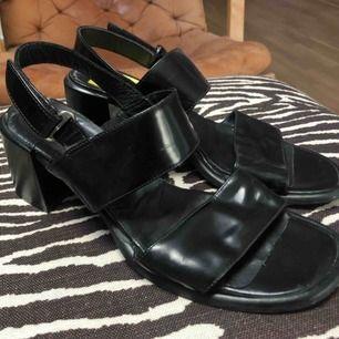 Fina svarta sandaletter med tjock klack. I svart läder och lack, gjorda i Italien. Strl. 39  Köpta secondhand på Emmaus. Då jag redan har ett par liknande tänker jag att någon annan kan få mer användning för dem! Tillägg för frakt eller mötas upp