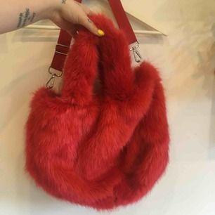 Stor röd pälsväska köpt på monki Använd fåtal ggr, perfekt skick Finns både axelrem som går att ändra längd på och handtag. Köparen står för frakt