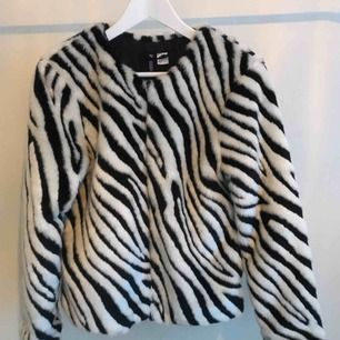 Zebramönstrad jacka i fuskpälsmaterial.  Storlek: 38 Aldrig använd av mig, och sparsamt använd av tidigare ägare, så i gott skick.   Frakt tillkommer