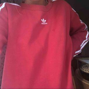 Röd sweatshirt från adidas i fint skick, knappt använd. Ganska oversized på mig som har xs. Köparen står för frakt :)