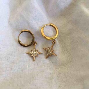 Guldpläterade huggie hoops med en söt stjärn-berlock från Orelia Jewellery. Använda några gånger men fortfarande i toppskick! Priset är inklusive frakt