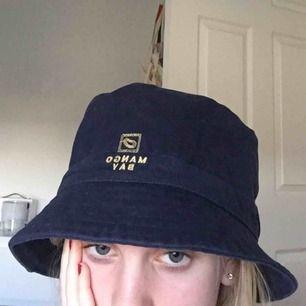 """Asball mörkblå buckethat med texten """"Mango Bay"""". Köparen står för frakt 🥳"""