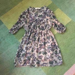 147b5908b302 Vacker blommig klänning med något genomskinliga armar.