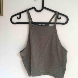 Grönbrunt linne, avklippt storlekslapp men förutom det är det i fint skick.