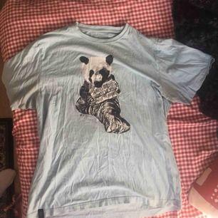 Ljusblå T-shirt men print av en panda som tigger.  Fint skick!