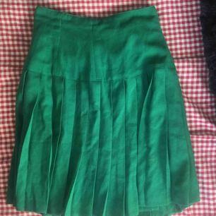 Söt grön kjol i school girl stil. Den är lite åt det längre hållet men med ett skärp kan en justera den hur du vill! Finfint skick