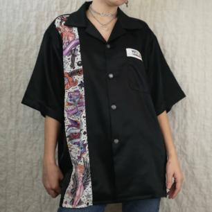 Skitsnygg silkig bowlingskjorta med helsvart rygg och en strimma med mönstrat tyg fram samt texten