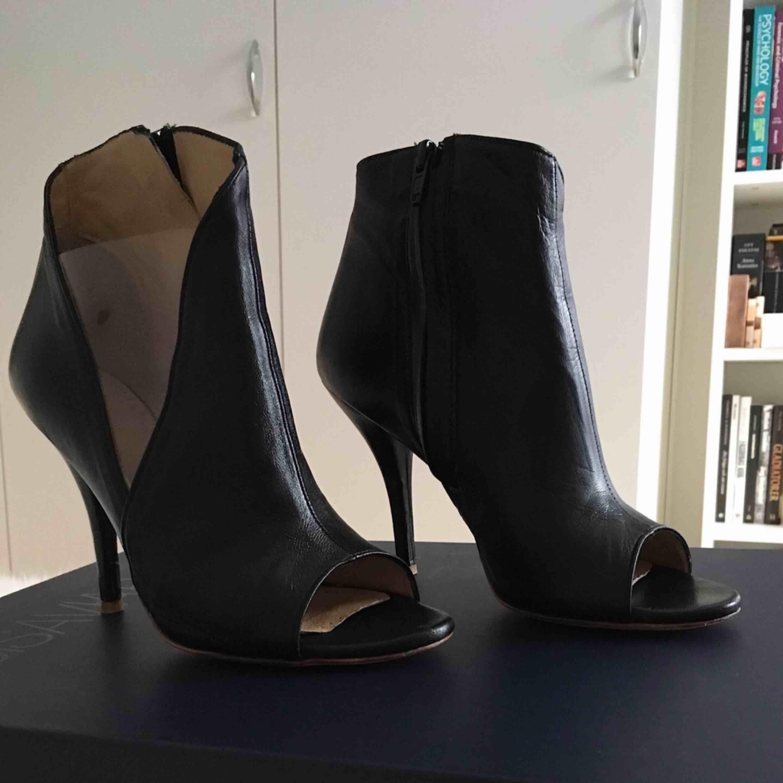 """Marc Ellis boots i läder och öppen tå. Ena sidan på skon har en gömd dragkedja, andra sidan har en """"öppning"""" med en transparent plastdetalj. Klacken är låg vilket inte gör dem obekväma att gå i.  Använda en gång. Storlek 38 Nypris: 1725 kr. Skor."""