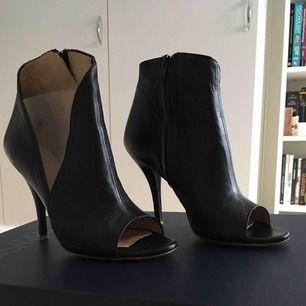 """Marc Ellis boots i läder och öppen tå. Ena sidan på skon har en gömd dragkedja, andra sidan har en """"öppning"""" med en transparent plastdetalj. Klacken är låg vilket inte gör dem obekväma att gå i.  Använda en gång. Storlek 38 Nypris: 1725 kr"""