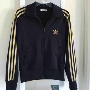 Adidas tröja med guldiga ränder. Storlek 38 men liten i storlek, passar storlek 36.