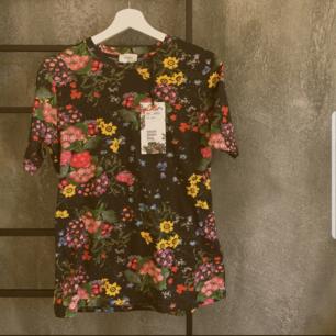 Oanvänd t-shirt från HMs kollektion med Erdem. Nypris 299kr, väldigt bra o skön kvalitet på bomullen, sålde ut väldigt snabbt. Köparen står för frakt. Kan ta foto med den på om det önskas :)
