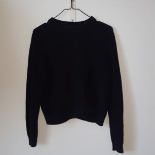 En svart stickad tröja med ett