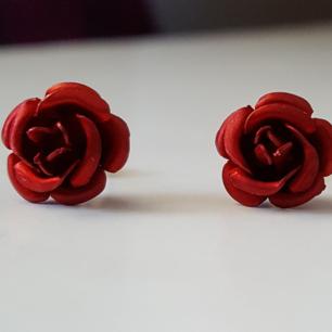 Silvriga örhängen i metall med röda rosor. Kan skickas om köparen står för frakten.