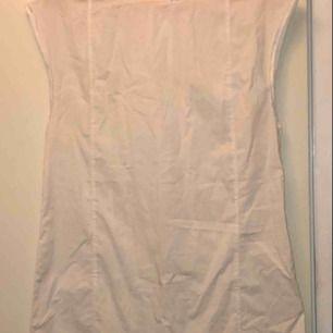 """Somrig vit klänning i """"skjort-material"""". Tunn, lätt, skön, hänger rakt på kroppen."""
