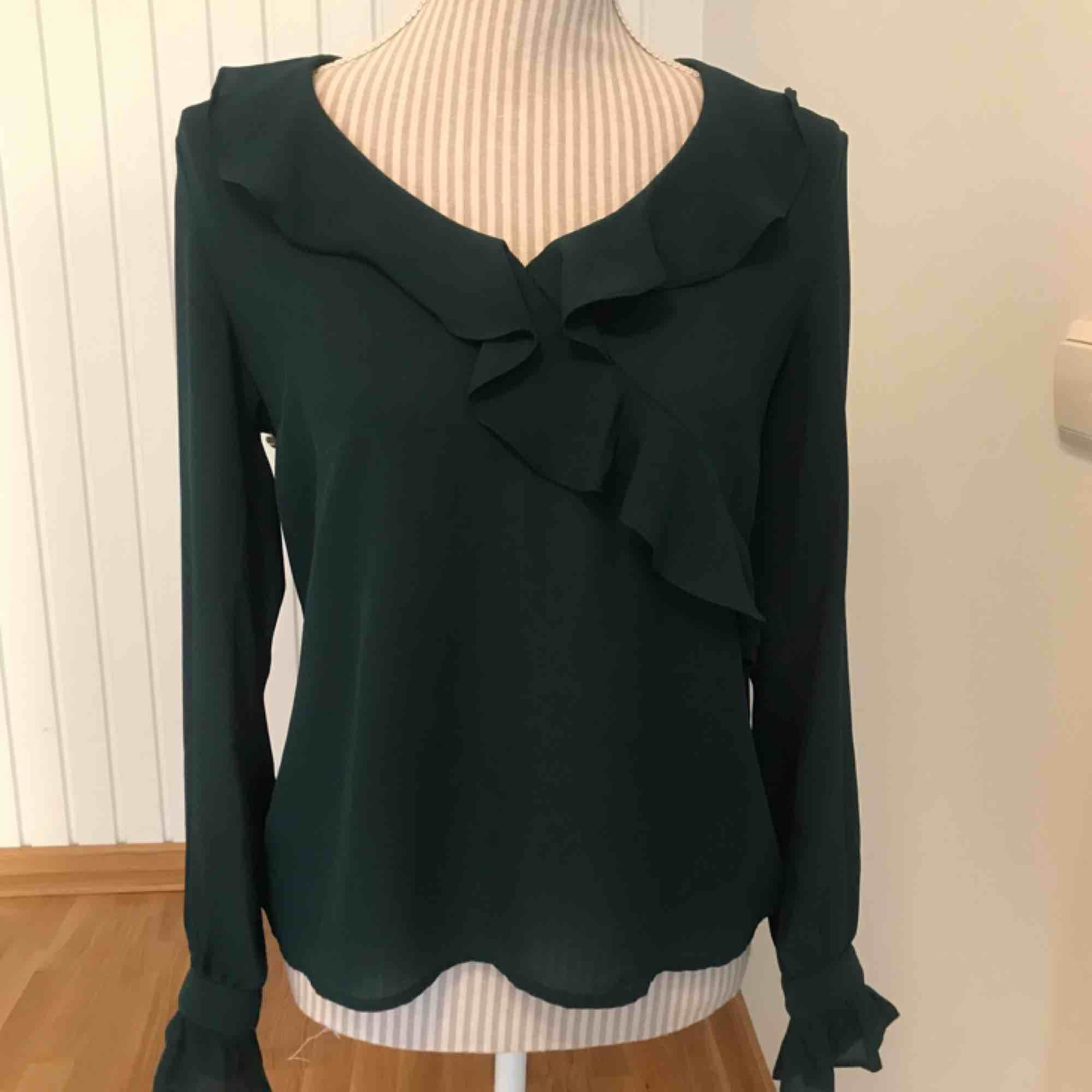 Knappt använd grön blus med volanger från Ginatricot 🌟 frakt på 40 kr tillkommer. Blusar.