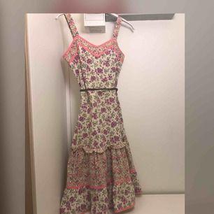 Vintage Hennes & Mauritz klänning 70 tal Klänningen är i fint skick, fint blommönster med fina rosa band. Det finns en svag fläck fram, men den syns knappt alls bland blommönstret Ca mått mätt rakt över Armhåla:42cm Midja:36-37cm Längd:97cm Kan skickas