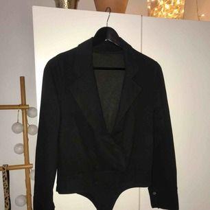 Snygg body. Ur-ringad i kostymliknande material. Aldrig använd, enbart testad men tyvärr för liten för mig.