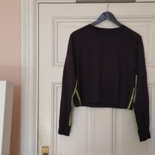 Långärmad, svart tröja med neongröna revärer från Cheap Monday.  Helt ny med lappen kvar! 100% ekologisk bomull✨