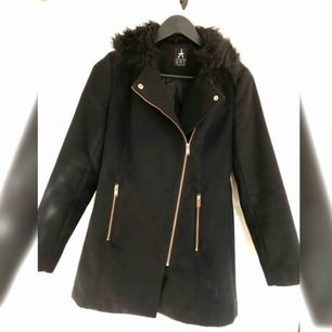 Svart lätt figursydd kappa med svart fejkpäls krage, rosé färgade dragkedjor som detaljer. Använd en höst säsong, strl 34