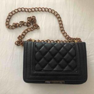 En svart handväska från ginatricot med guld kedja