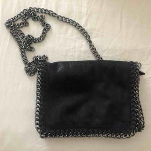 En svart handväska i mockaillusion med glitter. Frakt tillkommer.