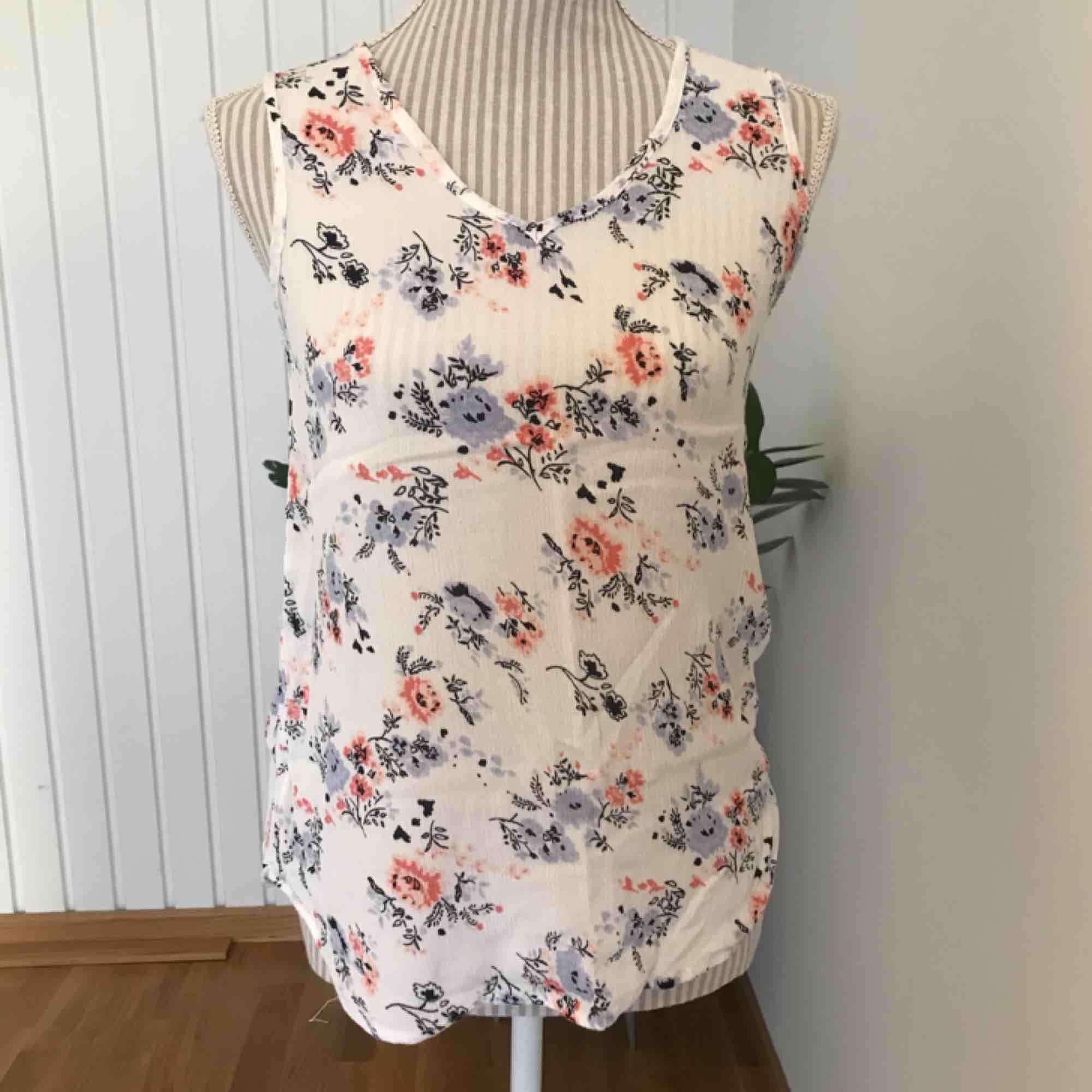 En vit blus från märket KAFFE med blåa och rosa blommor i fint skick! Storlek 36. Frakt på 40 kr tillkommer . Blusar.