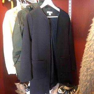 Marinblå kappa från hm, jättefin på. Använd ett fåtal gånger, i fint skick. Perfekt nu på våren/sommaren