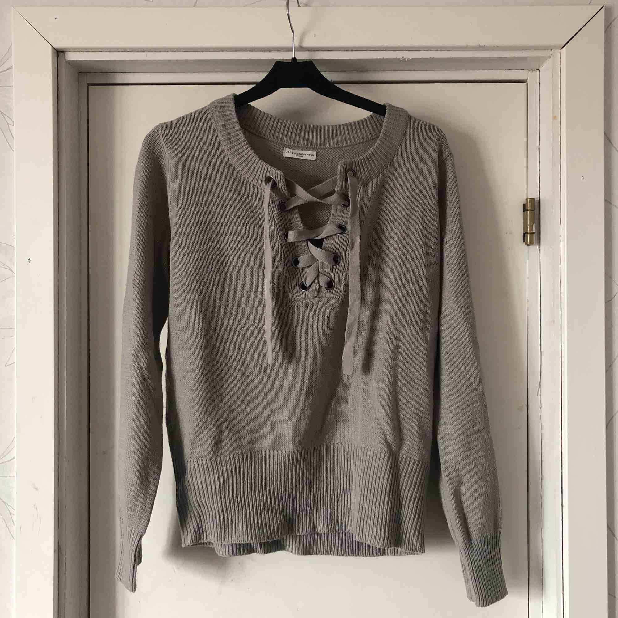 En grå stickad tröja. Väldigt skönt material och använd 2 gånger. Snyggt att styla tröjan lite olika med snörningen. Frakt tillkommer eller mötas upp i Karlstad . Tröjor & Koftor.
