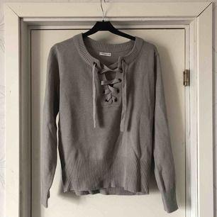 En grå stickad tröja. Väldigt skönt material och använd 2 gånger. Snyggt att styla tröjan lite olika med snörningen. Frakt tillkommer eller mötas upp i Karlstad